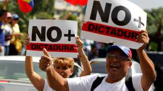 """Demonstrators carrying signs that reads """"no more dictatorship"""" rally during the so-called """"mother of all marches"""" against Venezuela's President Nicolas Maduro in Caracas, Venezuela April 19, 2017. REUTERS/Christian Veron"""