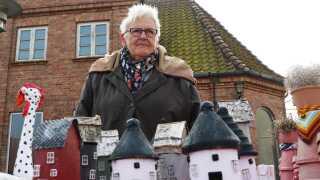 Jette Rømer Oldentoft engagerer sig meget i lokalmiljøet på Bornholm. Her deltager hun i et marked på torvet i Aakirkeby, hvor hun sælger små nips-rundkirker.