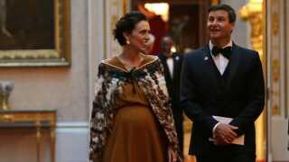 Her ses New Zealands premierminister sammen med sin mand, Clarke Gayford, under en middag på Buckingham Palace i London i april.