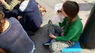 Greta Thunberg holder frokostpause i skyggen af en pæl foran Riksdagen. Menuen står på vegansk falafel-durum. (Foto: Annika Wetterling)
