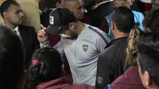 Boca Juniors' midtbanespiller Pablo Perez ankommer her til stadion efter en tur på hospitalet. Angiveligt blev han ramt af glas fra de splintrende ruder i øjet.