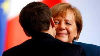 Den tyske kansler, Angela Merkel, kindkysser her med den franske præsident, Emmanuel Macron. De to indgik i sidste uge et kompromis om gasrørledningen.