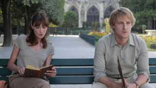 Her sidder skuespillerne Carla Bruni og Owen Wilson foran Notre Dame i filmen 'Midnight in Paris'.