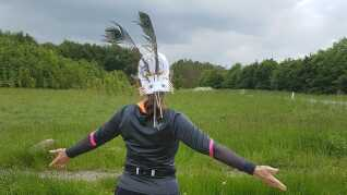 Lisbeth Preil har fundet en effektiv metode til at forhindre musvåge-angreb: en kasket med fjer og øjne i nakken.
