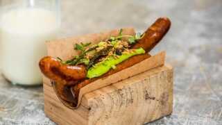 Sådan ser Danmarks bedste hotdog ud. Brødet er et sødmælksbrød, som er dampet og friturestegt, pølsen gemmer på havartiost og syltede citroner, og så er den toppet med skovæblecreme, blåskimmelost, løvstikkecreme, chipotle-mayo, friske sennepskorn og friterede hvidløgsflager.