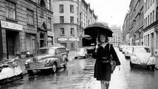 Tove Ditlevsen i regnvejr i sin barndoms gade, Hedebygade, på Vesterbro i København. Hendes roman 'Barndommens gade' er én af Nanna Mogensens anbefalinger.
