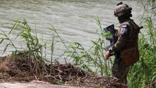 En mexicansk politimand patruljerer området, hvor ligene af en ung mand og hans datter blev fundet. Fotoet, der har skabt stor debat i USA, kan ses længere nede i artiklen.