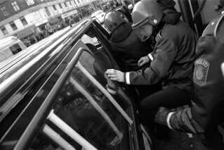 Politi har netop fået Pia Kjærsgaard ind i en vogn udenfor Unibank på Nørrebrogade 24. marts 1998, efter at hun var blevet angrebet af rasende unge.