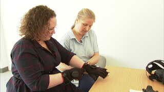 Dinna Jensen tager specialdesignede handsker på, når hun skal genoptræne med virtuel reality.