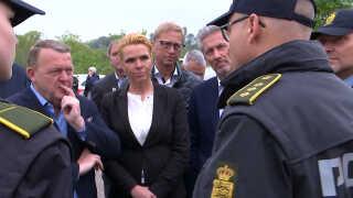 De tre V-topfolk snakker med udstationerede betjente ved grænsen.