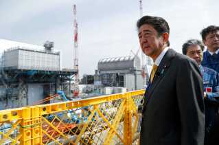 Japans premierminister, Shinzo Abe, besøgte søndag Fukushima. I baggrunden ses reaktor 2 og 3.