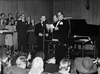 Landet over viser biograferne lige nu filmen 'Gøg og Gokke', der handler om komikerparret og stumfilmstjernerne Stan Laurel og Oliver Hardys personlige forhold. Filmen beskæftiger sig nu ikke med oktober 1947, hvor de to herrer opholdt sig i Danmark det meste af måneden og blev modtaget som helte. De besøgte også DR - endda på den allersidste dag under deres besøg. Gøg og Gokke besøgte DR i Radiohuset på Frederiksberg, hvor de blev præsenteret for publikum af programsekretær Svend Petersen. Han var én af DR's store navne på det tidspunkt, og han blev senere DR's programchef. I 1947 var fjernsynet endnu ikke kommet til Danmark, og et af de mest aflyttede programmer var weekend-aftenprogrammet 'Weekend-Hytten', som blev sendt direkte mellem 21.00 og 22.00. Her blev Gøg og Gokke - Stan Laurel og Oliver Hardy - interviewet. Programmet findes desværre ikke mere, og dette er det eneste foto, DR ligger inde med fra begivenheden.