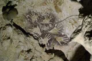 Oldgamle kunstværker af håndaftryk fundet i en grotte i Borneo. Der er to forskellige slags oven i hinanden med mindst 20.000 år i mellem, mener forskere.