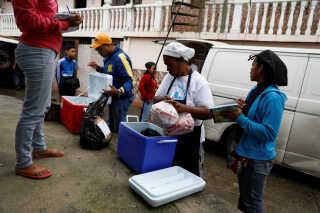 Velgørenhedsorganisationer deler mad ud til befolkningen i det fattige kvarter La Vega i hovedstaden Caracas.