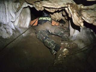 Grotten, hvor drengene forsvandt, forgrener sig i gange og tunneller, hvoraf nogle af smalle og svære at komme igennem. Her søger en redningsarbejder efter alternative indgange ind i grotten.