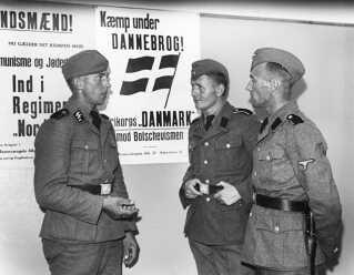 Tre danske østfrontsfrivillige foran hverveplakater for Frikorps Danmark.