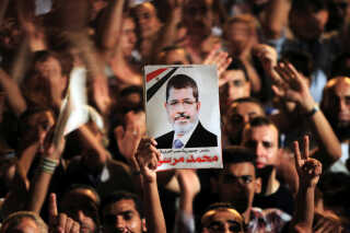 Demonstranter holder et foto af Mohamed Mursi under en demonstration på Tahrir-pladsen i Kairo i 2012.