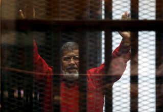 Mohamed Mursi hilser på tilhørere under et retsmøde i 2015.