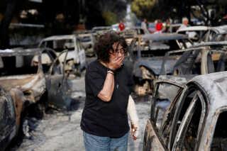 En kvinde reagerer på synet af den udbrændte landsby Mati nær Ahten i juli 2018.