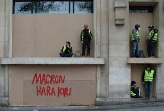 Demonstranter får sig et hvil. Med graffiti er skrevet 'Macron Hara Kiri'.    Om det er en opfordring til præsidenten, vides ikke, men hara kiri er et fortidigt selvmordsritual for samuraier, der blev brugt af vanærede krigere for at undgå skammen.