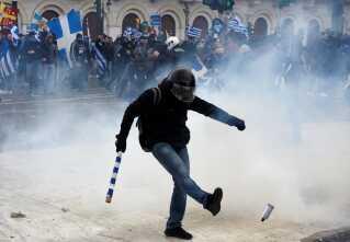 En demonstrant sparker en tåregasbeholder væk under dagens demonstration.