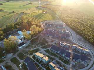 Permatopia i Karise består af 90 boliger fordelt i otte klynger med 10-12 rækkehuse i hver. Området er stadig under udvikling - der mangler blandt andet græs flere steder. Gården til venstre fungerer som fælleshus til samlinger. Den er under ombygning.