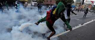 En demonstrant kaster en af politiets beholdere med tåregas efter betjente under demonstrationerne i Venezuelas hovedstad, Caracas.