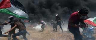 Palæstinensiske demonstranter forsøger at undvige tåregas ved grænsen mellem Israel og Gaza. Mere end 100 personer har mistet livet de seneste syv uger.