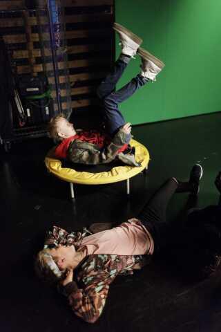 Morgan leger på en trampolin, mens Bastian tager en slapper på studiegulvet.