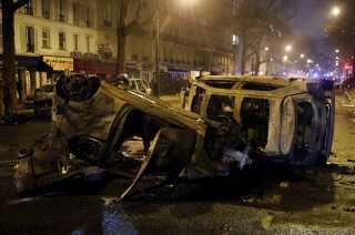 Afbrændte biler ses flere steder i Paris.