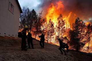 Brandmænd forsøger at redde hjem fra skovbranden.