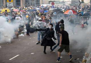 Det gik voldsomt for sig, da politiet i går lukkede demonstrationer i Hongkongs gader med tåregas og gummikugler.