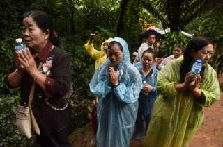 Familiemedlemmer til de forsvundne drenge er forsamlet i bøn i den silende regn nær grotten i Chiang Rai i torsdags.