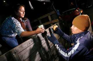 En colombianer giver mad til en venezuelansk mand på grænsen mellem Colombia og Ecuador. Ved grænserne stimler både demonstranter og nødhjælpsorganisationer sammen.