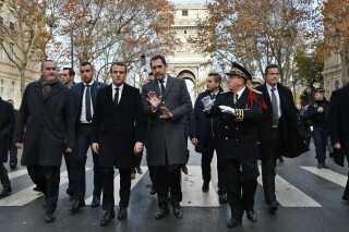 Frankrigs præsident Emmanuel Macron (forrest, til venstre) besøgte søndag området ved Triumfbuen, hvor urolighederne stod på lørdag.