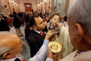 A boy is carried by his father as he receives Holy Communion during a mass on Christmas eve at Saint Joseph's Roman Catholic Church in Cairo, Egypt December 24, 2017. REUTERS/Amr Abdallah Dalsh