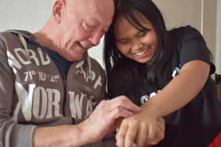 Christian Vestergaard og steddatteren Poy med et armbånd, som hun fik fra sin klasse.