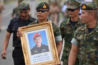 En æresvagt holder Samarn Poonans billede under en mindeceremoni i Rayong provinsen, Thailand.