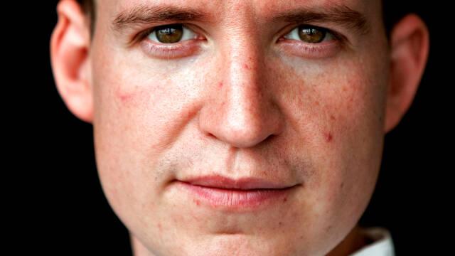 Portræt af Nicolai Tram med sort baggrund.