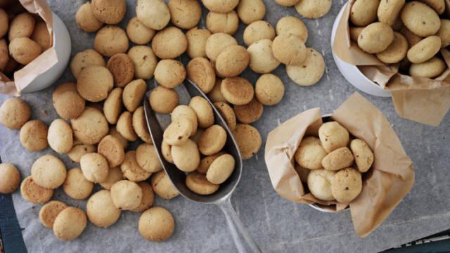 Pebernødder spredt på bagepapir og i poser.