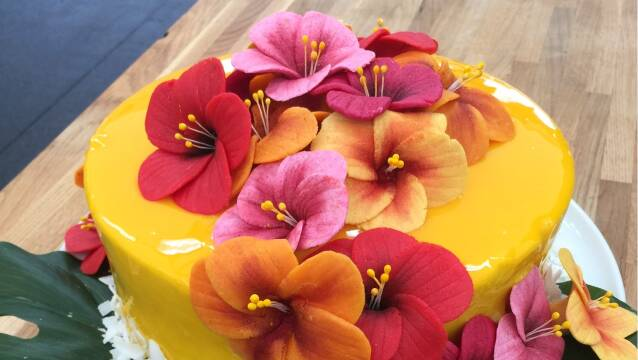 Eksotisk gul kage med blomster