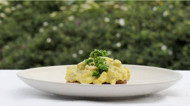 Tallerken med en rugbrødsmad med karrysalat