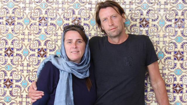 Anne Hjernøe og Anders Agger står op ad mønstret mur