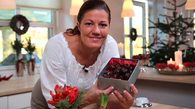 Mette Blomsterberg står lænet op ad bord med chokolader i æske