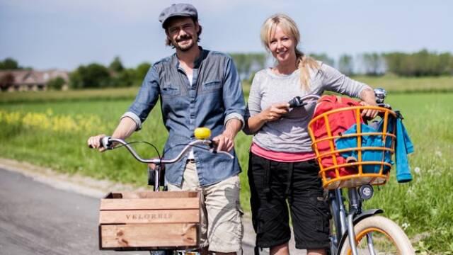 Puk og Herman står med hver sin cykel foran grøn mark