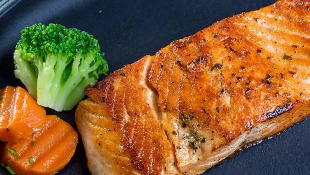 Et stegt stykke laks på en tallerken med broccoli og gulerod