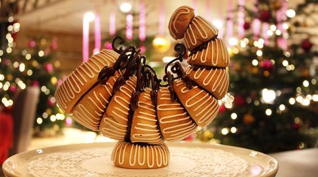 Billedet viser et smukt overflødighedshorn, lavet af kransekage og pyntet med fine chokolade-snirkler.