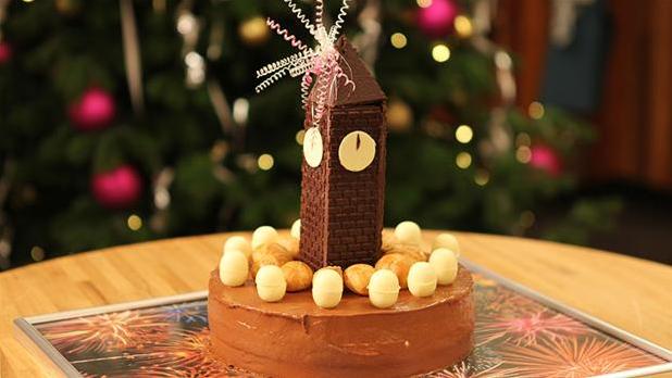 Billedet viser en festlig Klokken-24-kage, pyntet med chokolade som et nytårsur, der slår 12.