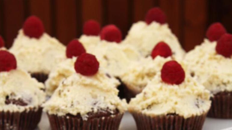 Billedet viser dejlige chokolade-cupcakes med chokoladecreme og nøddepynt.