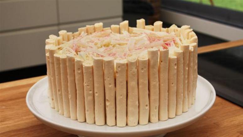 Billedet viser en lækker lagkage med en krans af marengsgrissiner.